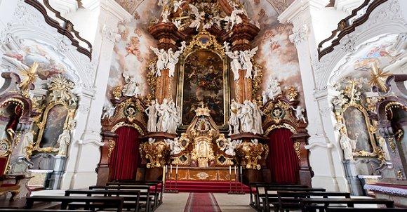 Ołtarz główny. Po jego bokach charakterystyczne dla baroku malarstwo iluzjonistyczne.