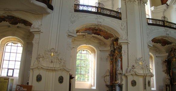 Rozglądając się po wnętrzu przybytku, wypatrujemy coraz to nowe detale.  Bogato zdobione boczne nisze okienne z obrazami, z freskami na sklepieniach, otoczone przez barokowe kolumny. Nad każdą z nich balkon.